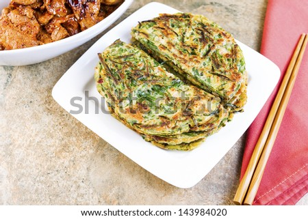 Horizontal photo of Korean green onion pancakes in plate, chopsticks on cloth napkin, and spicy barbequed pork in bowl on stone table - stock photo