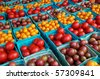 Horizontal photo of large group of cherry and grape tomatoes in boxes at farm market - stock photo