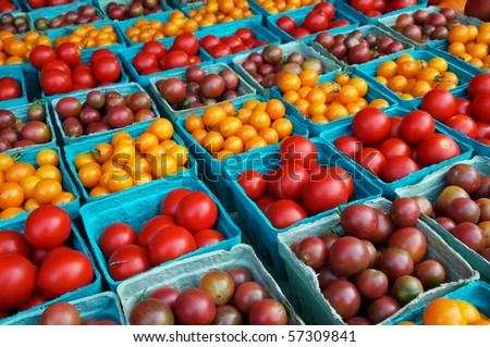 Horizontal photo of large group of cherry and grape tomatoes in boxes at farm market
