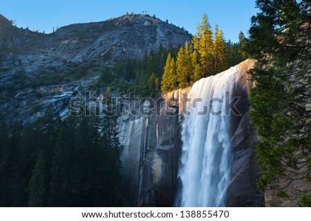 Horizontal photo of light hitting the top of Vernal Falls along the Mist Trail in Yosemite National Park. - stock photo