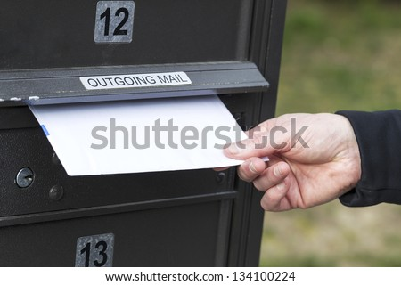 Horizontal photo of male hand putting letters into outgoing postal mailbox with green grass in background - stock photo