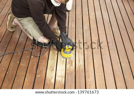 Horizontal photo of mature man kneeling while sanding outdoor wooden deck