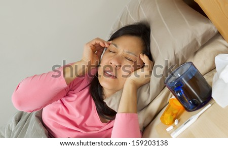 Horizontal photo of mature woman holding her head in pain while lying in bed sick - stock photo