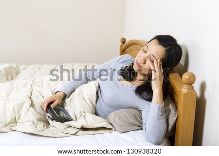 Horizontal photo of mature woman, with fingers against head, while holding alarm clock in other hand - stock photo