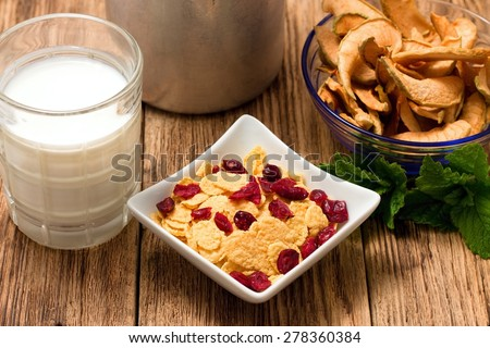 Horizontal photo of modern square bowl full of cornflakes with fruit. Glass of milk and other bowl with dried apple are around. All is placed on old wooden table. - stock photo