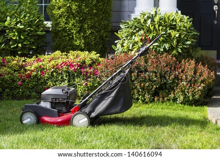 Horizontal photo of old gas lawnmower on front yard with home in background - stock photo