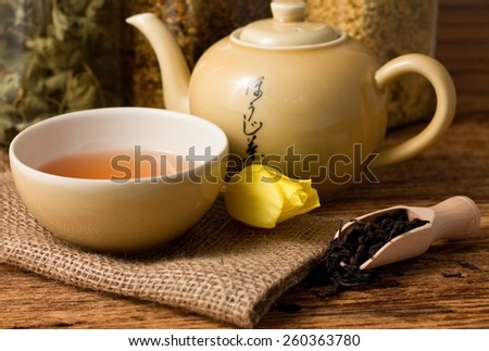 Horizontal photo of Oriental tea set on jute cloth and tulip bloom and wooden spoon with dry tea leafs everything placed on old worn wooden table - stock photo