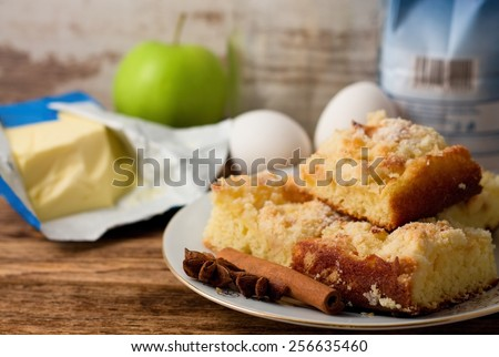 Horizontal photo of Plate with several portions of apple cake and spice, anise and cinnamon with butter, apple, eggs and flour in background placed on old worn wooden board - stock photo
