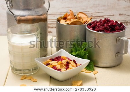 Horizontal photo of scene consists of white square bowl with cornflakes, two cups with dried berries and apples, glass of milk, green herbs and aluminum can. Few cereals are spilled around. - stock photo