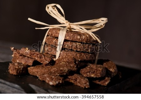 Horizontal photo of several cereal biscuits placed in a stack bonded by yellow straw placed on piece of black stone. Few broken pieces are placed around.  - stock photo