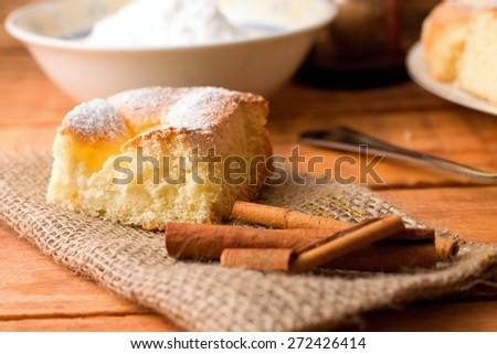 Horizontal photo of single portion of curd fresh cake on jute cloth together with few pieces of cinnamon. Powder sugar in white bowl and spoon in background. All placed on wooden table. - stock photo