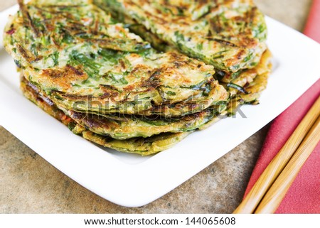 Horizontal photo of stacked Korean green onion pancakes in plate, chopsticks on cloth napkin with stone table underneath - stock photo