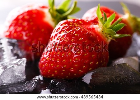 Horizontal photo of three fresh juicy strawberries. Strawberries with red color on black slate stone. Water and ice on slate stone. Few strawberries with green stalks. - stock photo