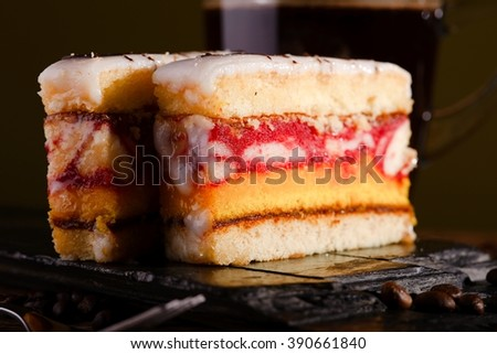Horizontal photo of two slices of sweet desert with color layers on sugar on the top placed on piece of black stone. Cup of coffee is in background on wooden board with few coffee grains around. - stock photo