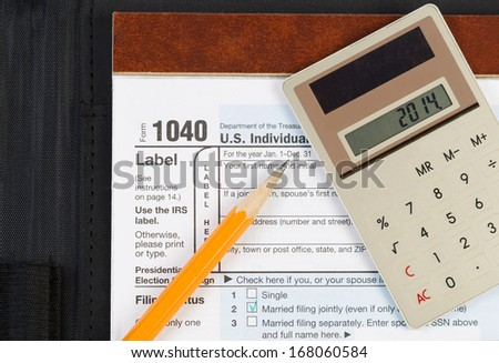 Horizontal photo of United States Tax Form 1040, for Individual Income, with Calculator and pencil on nylon business folder - stock photo