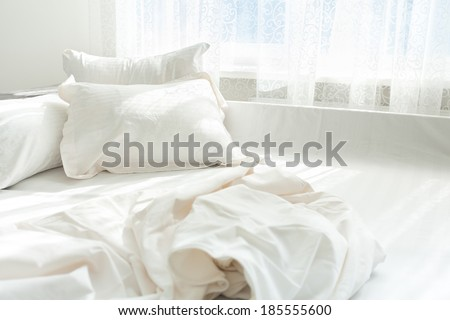 Horizontal photo of untidy bed against window - stock photo