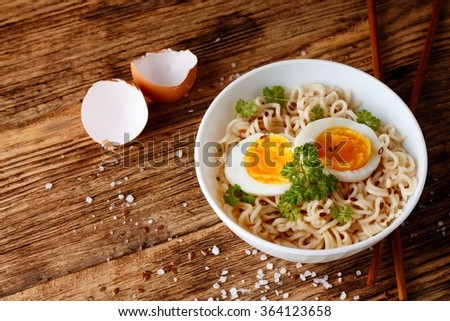 Horizontal photo of white bowl full of chinese soup with long noodles. Two slices of egg and green parsley are inside. Salt, fluxseeds, shells and chopsticks are around. - stock photo