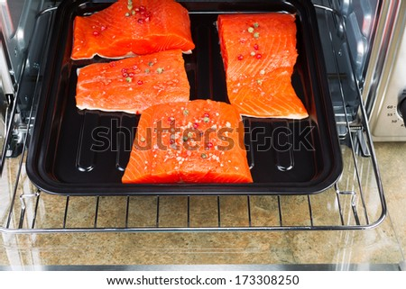 Horizontal photo of Wild Red Salmon pieces coated with dried red peppercorns and sea salt inside oven with stone counter top underneath  - stock photo