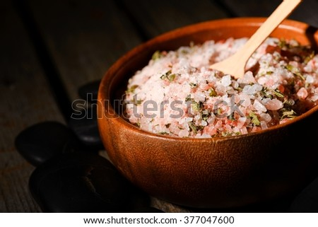 Horizontal photo of wooden bowl full of bath pink sea salt with herbs inside. Bowl is placed on old wooden board with few black stones around.  - stock photo
