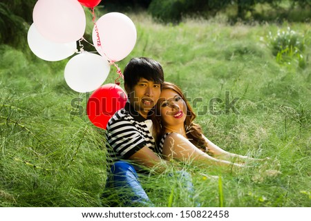 Horizontal photo of young adult couple, sitting in the middle of a tall grass field, with several white and red balloons while expressing love by holding each other    - stock photo