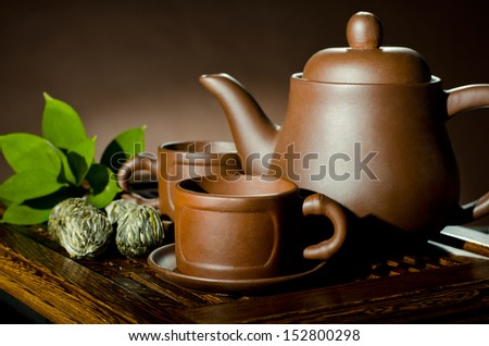 horizontal photo, still life of the clay teapot and  cup on brown background - stock photo