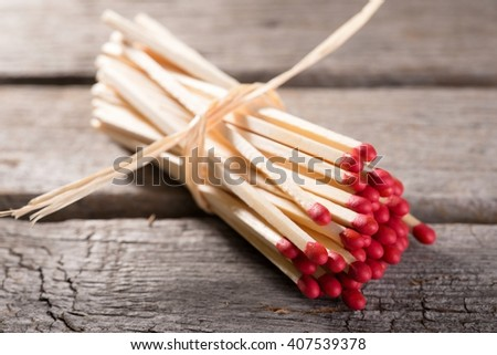 Horizontal photo with Bunch of long wooden matchsticks with red heads which are bonded by piece of yellow dry straw. Bunch is placed on old worn wooden board with grey color. - stock photo