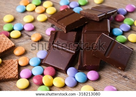 Horizontal photo with many colorful chocolate coated sweets among long biscuits and pieces of broken dark chocolate. All is placed on wooden board. - stock photo