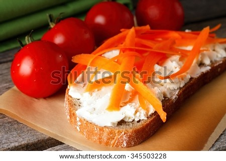 Horizontal photo with slice of bread with fresh cottage cheese and several carrot shaves. Few red tomatoes are around with green towel on paper and wooden board.  - stock photo