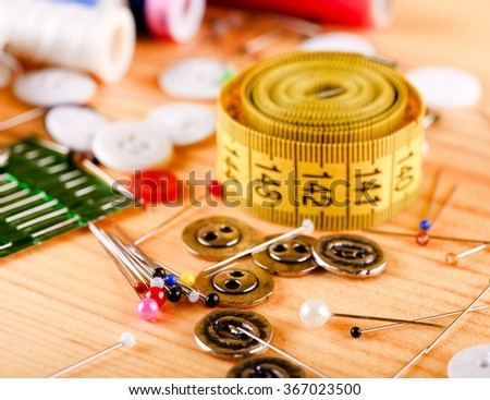 Horizontal photo with tailoring accessories placed on light wooden color like color pins, tape measure, several knobs, needles and seeings. - stock photo