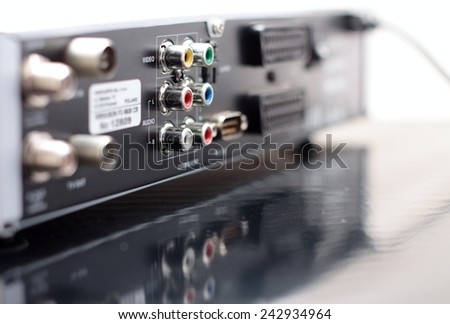 Horizontal Picture of rear side of music and video player with focus on color audio connectors in two rows and with visible reflection in the surface of bottom board - stock photo
