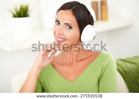 Horizontal portrait of a beautiful carefree woman listening to music on headphones while touching her chin