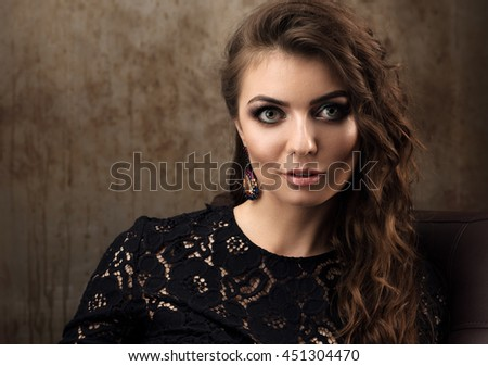 Horizontal portrait of a beautiful young woman in a black lace dress. Long wavy hair and professional makeup. The interior in the style loft