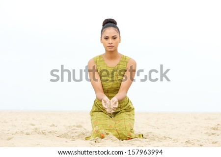 Horizontal portrait of a beautiful young woman sitting at the beach with sand flowing from hand - stock photo