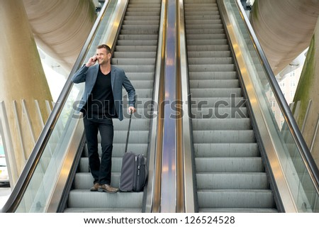 Horizontal portrait of a business man talking on the phone while going down escalator - stock photo