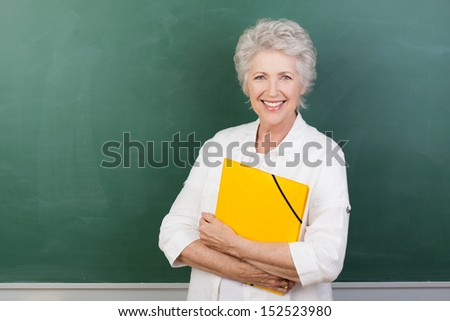 Horizontal portrait of a Caucasian cheerful female senior teacher holding a yellow file with a blank chalkboard behind - stock photo