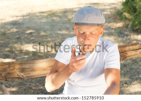 Horizontal portrait of a Caucasian man lighting a cigarette while relaxing sitting on a bench in the park - stock photo