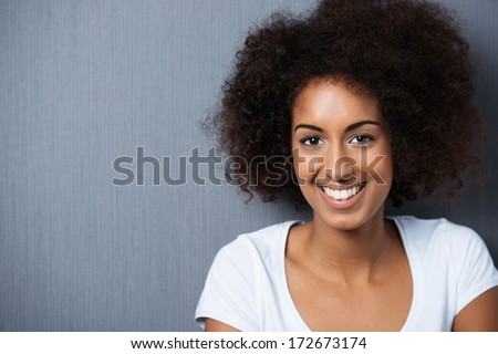 Horizontal portrait of a cheerful African American attractive young woman, wearing a white T-shirt, while smiling with perfect teeth and looking at camera, on grey background - stock photo
