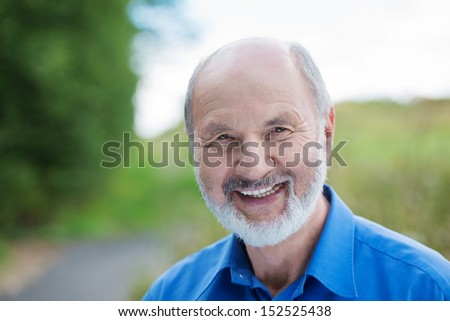 Horizontal portrait of a happy Caucasian retired bearded man, outdoors with a blurred green area in the background - stock photo