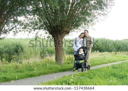 Horizontal portrait of a happy family walking outdoors with baby