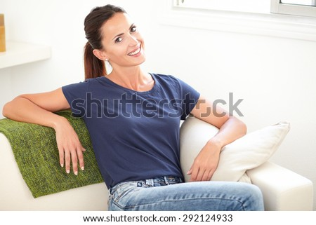 Horizontal portrait of a happy young woman in blue shirt smiling at the camera