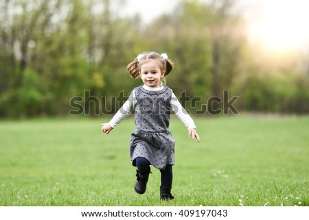 horizontal portrait of a little girl running in the green grass in a big field with a happy face expression on a sunny spring day with trees and sunshine in the background