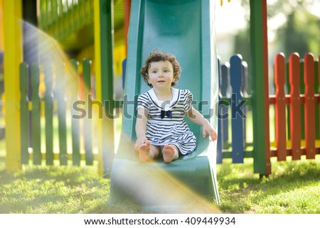 horizontal portrait of a little girl sitting on a slide in a playground wearing a cute blue dress with a ribbon on a sunny summer day with painted wooden fence and nature in the background