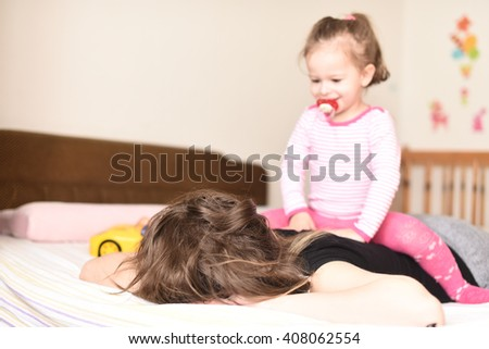 horizontal portrait of a little girl sitting on her mother's back while she sleeps in the bedroom on the bed with a pacifier in her mouth, a yellow toy car and wall decorations in the background - stock photo
