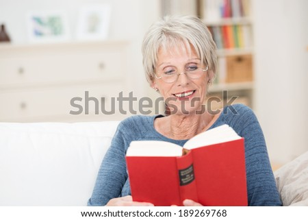 Horizontal portrait of a retired Caucasian amused woman reading an interesting book with red covers while sitting on the sofa at home - stock photo