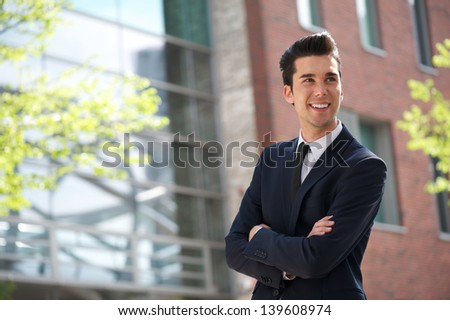 Horizontal portrait of a young businessman smiling outdoors - stock photo