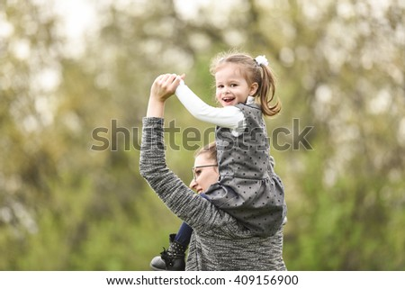 horizontal portrait of a young girl sitting on her mother's shoulders, happy and showing teeth, walking in a park in nature and holding hands up in the air in spring in daytime - stock photo