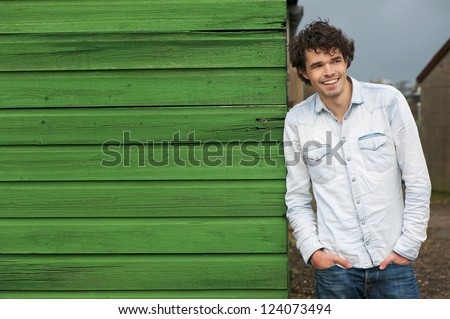 Horizontal portrait of a young handsome caucasian man smiling outdoor. Casual guy leaning against a green wooden wall. He is looking away and hands in pockets. Copy space friendly face - stock photo