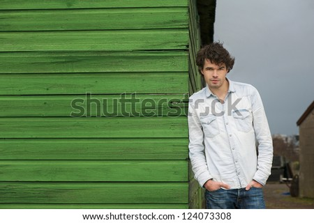Horizontal portrait of a young handsome caucasian man smiling outdoor. Male model leaning against green wooden wall and looking at camera. Copy space friendly face - stock photo