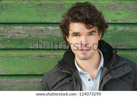 Horizontal portrait of a young handsome caucasian man smiling outdoor. Male model looking at camera. Copy space friendly face - stock photo