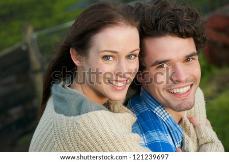 Horizontal portrait of a young, happy, smiling couple outdoor. Caucasian boyfriend and laughing girlfriend are enjoying the outdoors.
